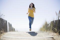 Mädchen, das auf Strand-Gehweg läuft Lizenzfreies Stockfoto