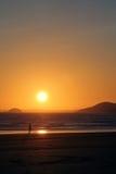 Mädchen, das auf Strand mit Sonnenuntergang geht Stockbilder