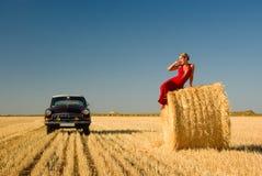 Mädchen, das auf Strohballen mit Retro- Autohintergrund sich lehnt. lizenzfreie stockbilder