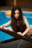 Mädchen, das auf sunbeds am Poolhintergrund liegt stockbild