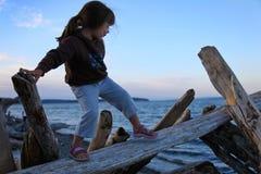 Mädchen, das auf Treibholz am Strand steigt Stockbild