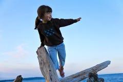 Mädchen, das auf Treibholz am Strand steigt Stockbilder