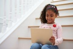 Mädchen, das auf Treppenhaus unter Verwendung Digital-Tablets sitzt lizenzfreie stockfotografie