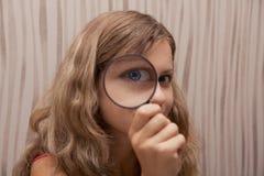 Mädchen, das auf Vergrößerungsglas schaut Lizenzfreie Stockbilder