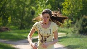 Mädchen, das auf Waldweg in einem Park läuft und Atem nachdem dem Rütteln holt Porträt der müden stillstehenden Athletenfrau, nah stock video