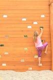 Mädchen, das auf Wand klettert Stockfotos