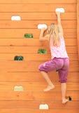 Mädchen, das auf Wand klettert Stockfotografie