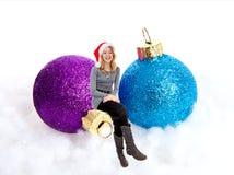 Mädchen, das auf Weihnachtskugeln sitzt Lizenzfreie Stockfotografie