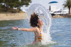 Mädchen, das aus dem Wasser heraus spritzt Stockbild