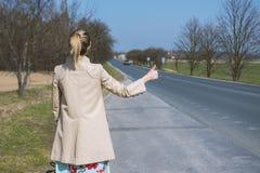 Mädchen, das Auto auf der Straße stoppt lizenzfreie stockbilder