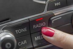 Mädchen, das Autoradio-Stereoplatte und moderne Armaturenbrettausrüstung bedrängt Lizenzfreie Stockbilder