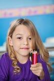 Mädchen, das Bündel Farbbleistifte in der Vorschule hält Lizenzfreie Stockbilder