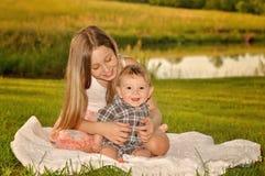 Mädchen, das Baby auf Decke kitzelt stockfotos