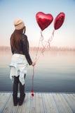 Mädchen, das Ballone auf einer Flussbank hält Stockfoto