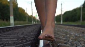 Mädchen, das barfuß entlang Eisenbahnschiene geht stock video