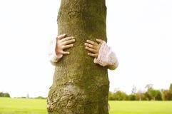 Mädchen, das Baum im Park umarmt. Stockfotografie