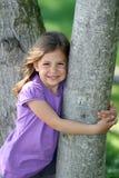 Mädchen, das Baum umarmt Lizenzfreies Stockbild