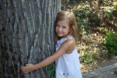 Mädchen, das Baumkabel umarmt Stockfotos