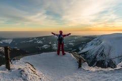 Mädchen, das bei dem Sonnenuntergang auf die Oberseite des Berges aufpasst Stockfoto