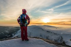 Mädchen, das bei dem Sonnenuntergang auf die Oberseite des Berges aufpasst Stockbild