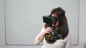 Mädchen, das beim Spielen eines Videospiels der virtuellen Realität mit VR-Gläsern während einer Testsitzung im Klassenzimmer ers stock footage