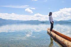 Mädchen, das beiseite schaut, stehend auf Kanu, zurück zu Kamera Stockfoto