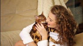 Mädchen, das Bengal-Katze spielt und beißt stock footage