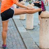 Mädchen, das bevor dem Laufen in Stadtmarathon ausdehnt lizenzfreies stockbild