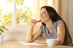 Mädchen, das bevor ein Brief denkt, geschrieben wird Stockfotografie