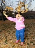 Mädchen, das Blätter spielt Lizenzfreies Stockbild