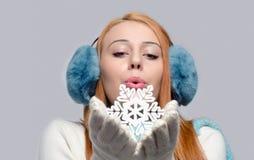 Mädchen, das blaue Ohrmuffen trägt und eine große gefälschte Schneeflocke durchbrennt Lizenzfreie Stockbilder