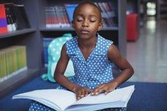 Mädchen, das Blindenschrift-Buch in der Bibliothek liest Lizenzfreie Stockbilder