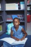Mädchen, das Blindenschrift in der Bibliothek liest Lizenzfreie Stockfotos
