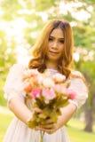 Mädchen, das Blume in einem Sommerpark übergibt Lizenzfreie Stockfotos