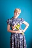 Mädchen, das Blumen auf einem blauen Hintergrund hält Lizenzfreies Stockfoto