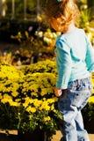 Mädchen, das Blumen auf Landwirt-Markt betrachtet Lizenzfreie Stockfotografie
