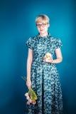 Mädchen, das Blumen und Schädel auf einem blauen Hintergrund hält Lizenzfreie Stockbilder