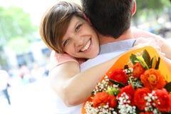 Mädchen, das Blumen vom Freund empfängt Lizenzfreie Stockfotografie