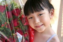Mädchen, das Blumenstrauß der Rosen lächelt u. anhält Lizenzfreies Stockbild