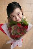 Mädchen, das Blumenstrauß der Rosen lächelt u. anhält Stockfotos