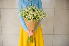Mädchen, das Blumenstrauß von camomiles hält Stockfotos