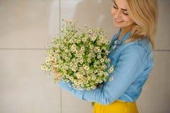 Mädchen, das Blumenstrauß von camomiles hält Stockbild