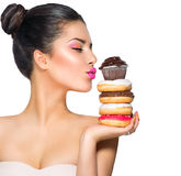 Mädchen, das Bonbons und bunte Schaumgummiringe nimmt Lizenzfreie Stockfotos