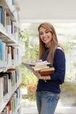 Mädchen, das Buch in der Bibliothek und im Lächeln wählt Lizenzfreie Stockbilder
