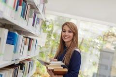 Mädchen, das Buch in der Bibliothek und im Lächeln wählt Stockfoto