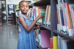 Mädchen, das Buch in der Bibliothek vorwählt lizenzfreie stockbilder