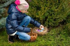 Mädchen, das bunte Ostereier im Korb am Hinterhof sammelt Stockfotografie