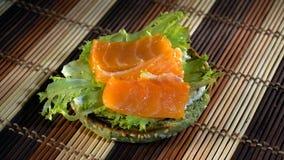 Mädchen, das Burger mit Stücken von Lachsen und von Tomate zubereitet stock footage