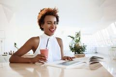 Mädchen, das Café im trinkenden lächelnden Blinzeln Smoothie stillsteht, Zunge zeigend Stockfotografie