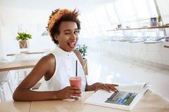 Mädchen, das Café im trinkenden lächelnden Blinzeln Smoothie stillsteht, Zunge zeigend Lizenzfreie Stockbilder